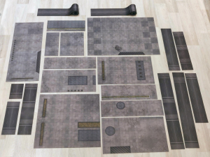 Cut-up parts of the cityscape battle mat laid out together on the floor