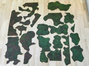 Cut-up parts of the forest battle mat laid out together on the floor